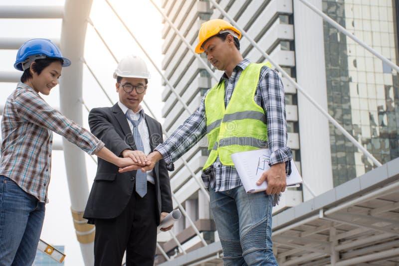 专业亚洲与城市背景一起的工程学队加入的手 库存照片
