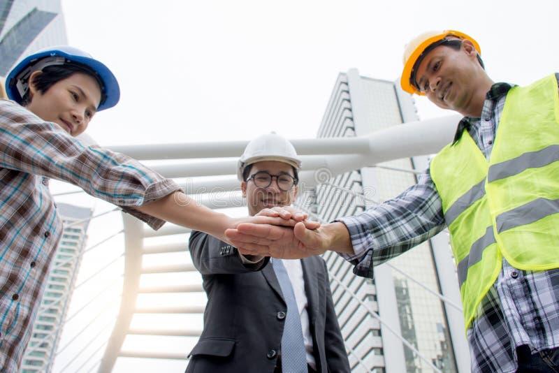 专业亚洲工程学队加入的手一起从低角度视图有城市背景 免版税图库摄影