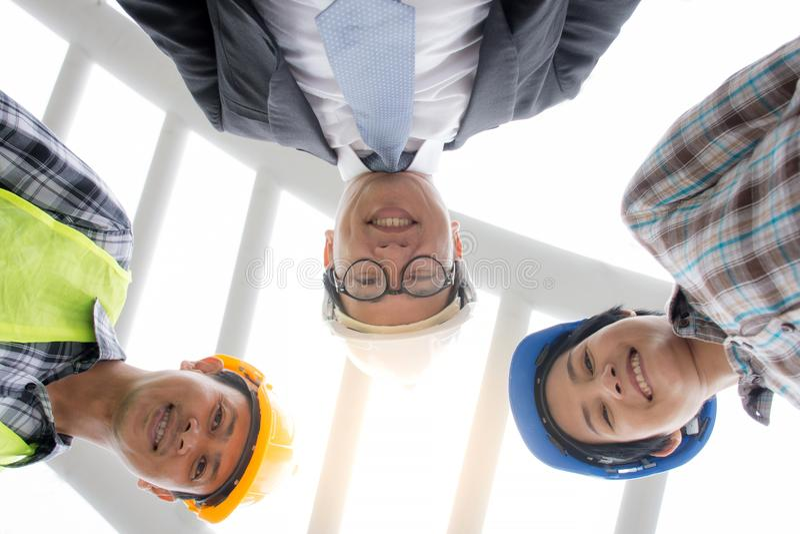 专业亚洲看从低角度视图的工程学队佩带的安全帽照相机 免版税图库摄影