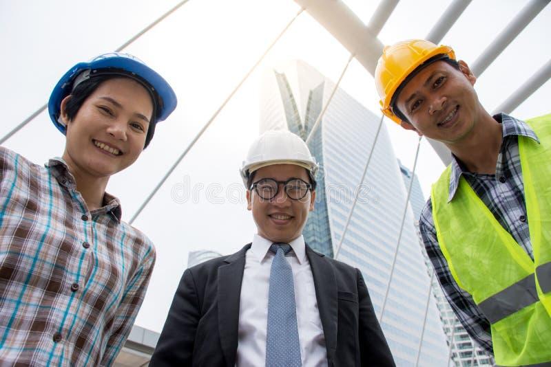 专业亚洲看照相机的工程学队佩带的安全帽 库存图片