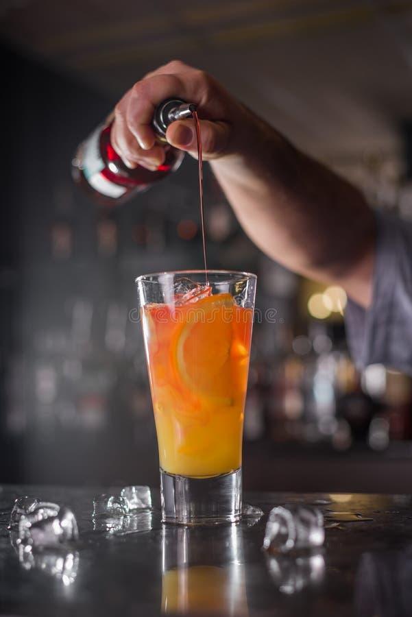 专业侍酒者准备并且混合倒从一个瓶的鸡尾酒红色糖浆在酒吧的背景 免版税图库摄影