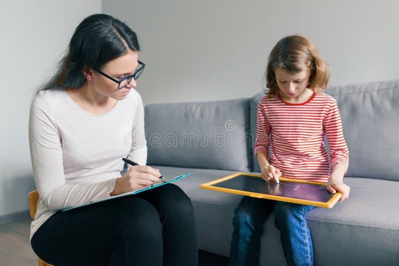 专业儿童心理学家谈话与儿童女孩在办公室,孩子画图画 免版税图库摄影