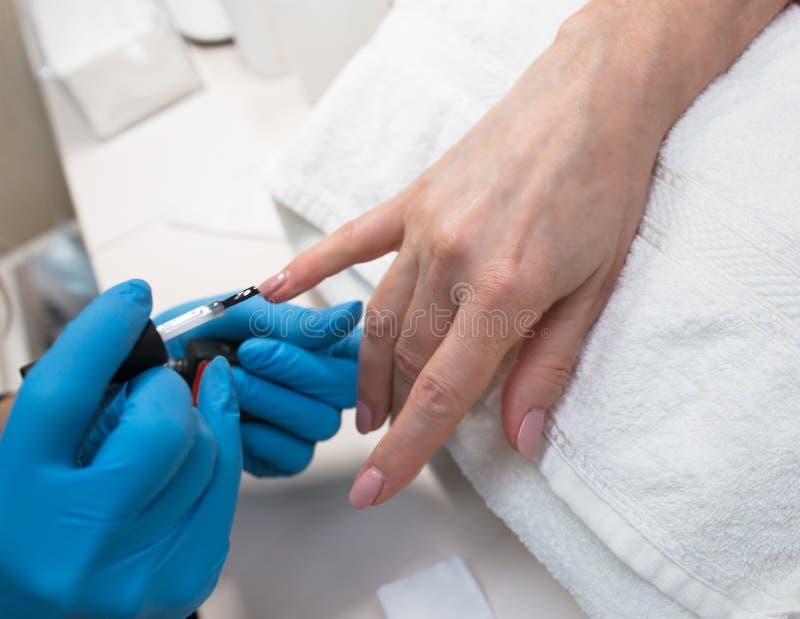 专业制造的修指甲特写镜头与透明光滑的acrilyc的 专家美容师在发廊修指甲师手上 免版税库存照片