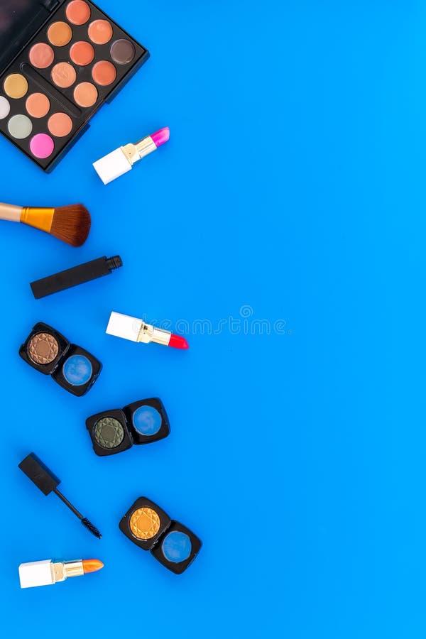 专业化妆用品设置与眼影膏调色板在蓝色背景顶视图空间的文本的 免版税库存照片