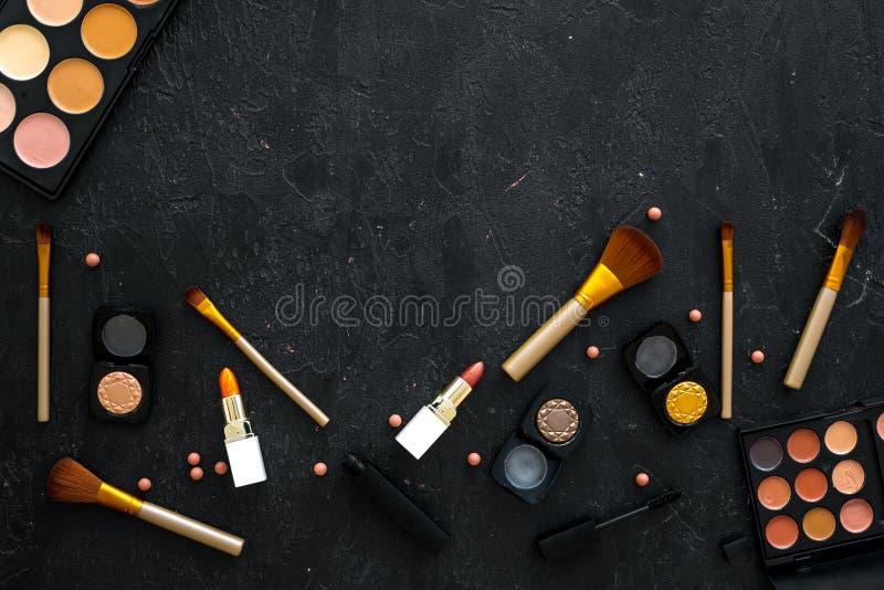 专业化妆用品设置与眼影膏调色板在黑暗的背景顶视图大模型的 免版税库存照片