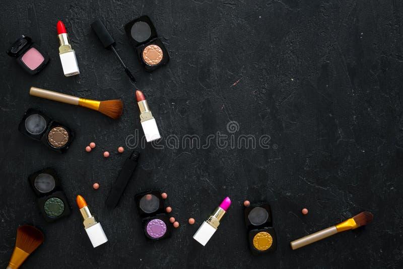 专业化妆用品设置与眼影膏调色板在黑暗的背景顶视图大模型的 库存图片