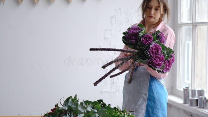 专业卖花人举行异常的紫色花 免版税库存图片