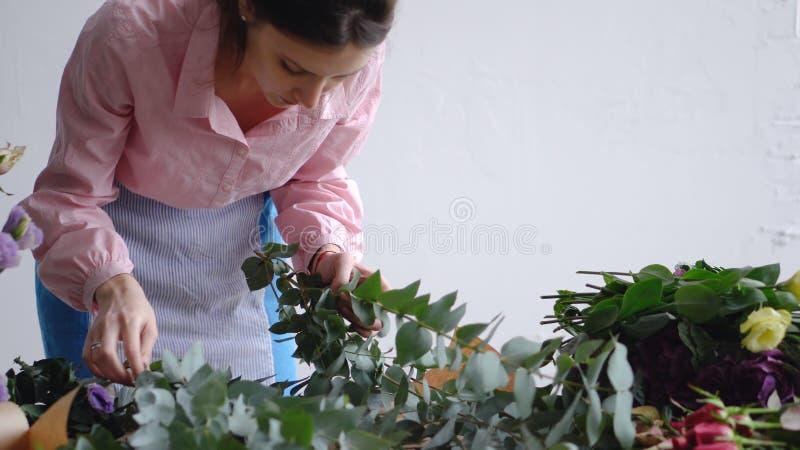 专业卖花人妇女做花束与玉树的美丽的花 免版税库存图片