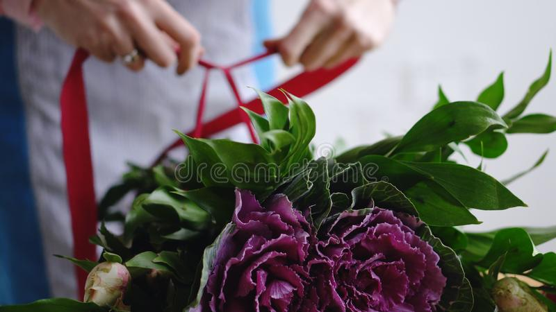 专业卖花人艺术家在背景中裹与丝带花束 免版税库存图片