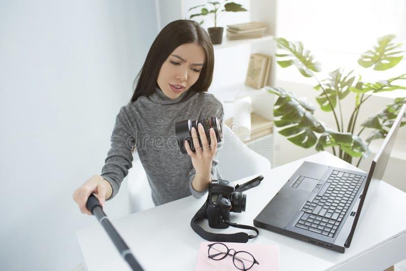 专业博客作者坐在桌上并且记录她看到照相机` s透镜和的录影 免版税库存图片