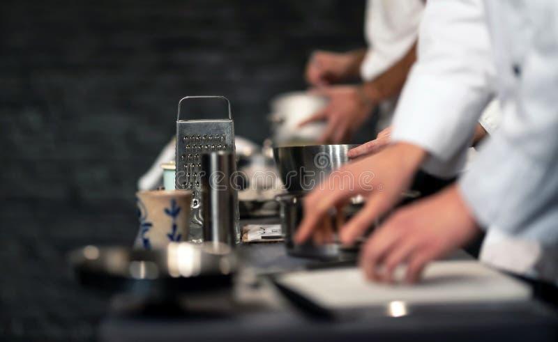 专业厨师团队在商业厨房准备食物 系统配餐生产过程中的厨师 内部 免版税库存图片