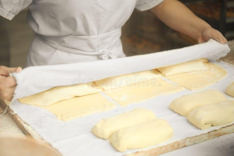 专业厨师滚动的面团在厨房里 商业面包店 库存图片
