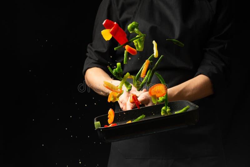 专业厨师 他准备与菜的一个盘在平底深锅 在黑背景,菜单,食谱书,健康食品 免版税库存照片