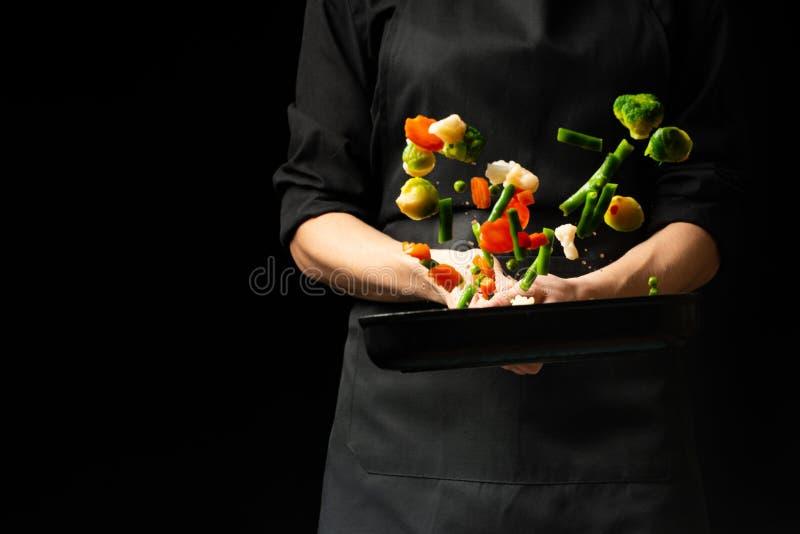 专业厨师 他准备与菜的一个盘在平底深锅 在黑背景,菜单,食谱书,健康食品 免版税库存图片