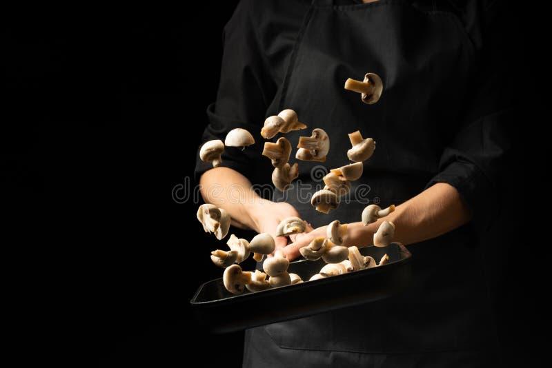 专业厨师 厨师准备一个盘用在平底深锅的蘑菇蘑菇 在黑色背景 菜单,食谱书, 免版税库存图片