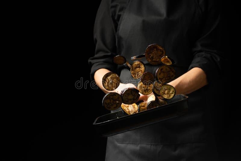 专业厨师 厨师准备盘用在平底深锅的茄子 在黑色背景 菜单,食谱书,健康食品, 库存照片