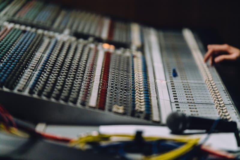 专业右手附近的soundboard由音频搅拌器控制板混合声音与按钮和滑子 库存照片