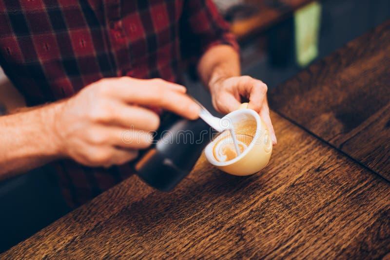 专业在咖啡,浓咖啡和创造一杯完善的可口热奶咖啡的barista倾吐的拿铁泡沫 免版税图库摄影