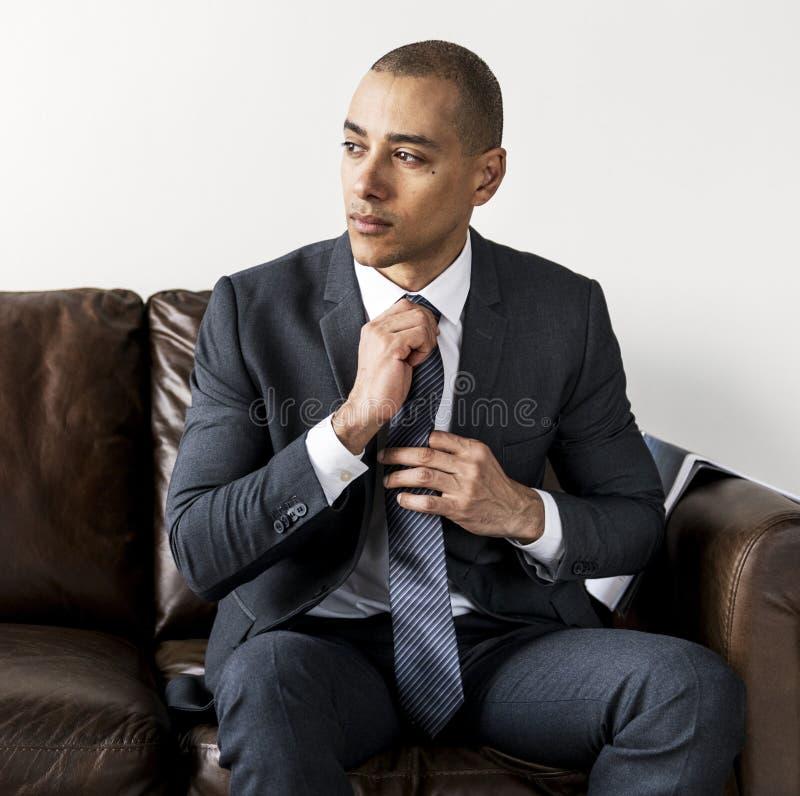 专业年轻商人坐沙发 免版税库存照片