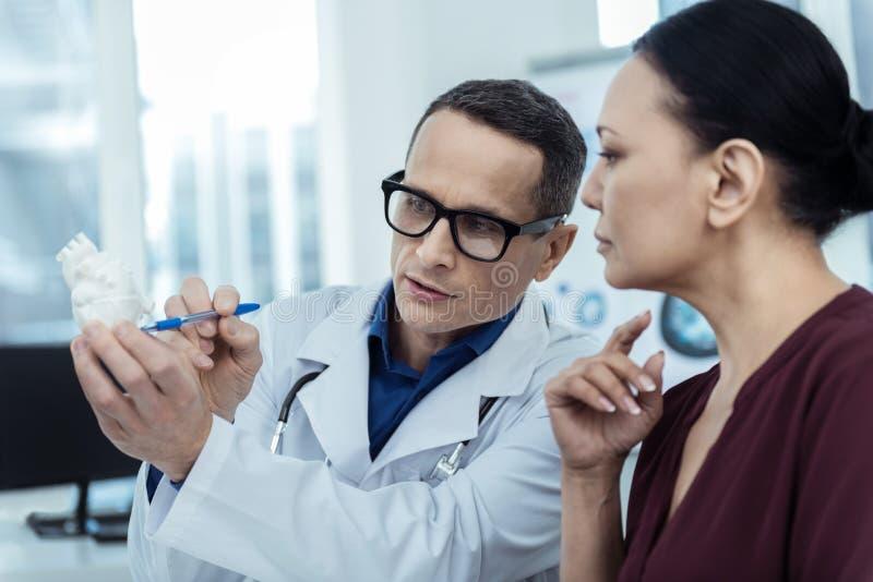 专业心脏科医师谈话与他的患者 库存照片