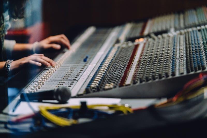 专业手附近的soundboard由音频搅拌器控制板混合声音与按钮和滑子在录音室 免版税库存图片