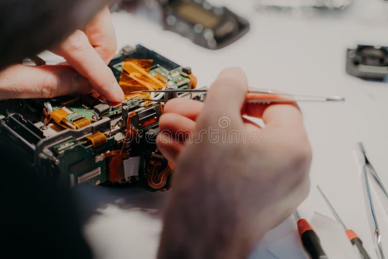 专业技术员修理在服务中心拆卸了照相机的部分,拿着镊子,工作 残破的透镜dslr r 免版税图库摄影