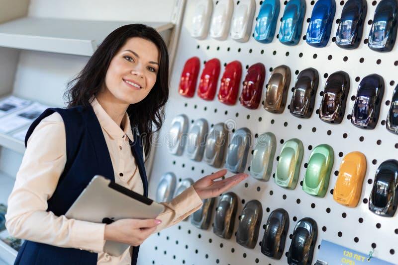 专业推销员帮助对选择了一辆汽车的颜色在经销权中心 免版税库存照片