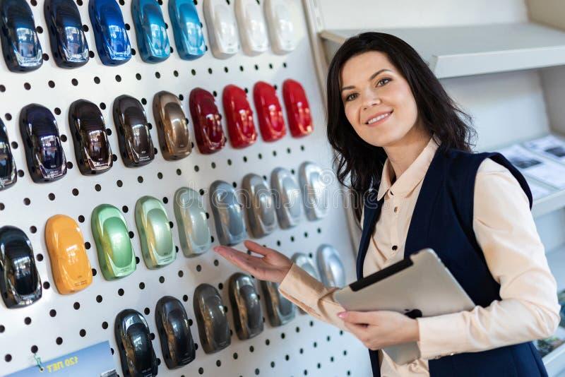 专业推销员帮助对选择了一辆汽车的颜色在经销权中心 库存图片