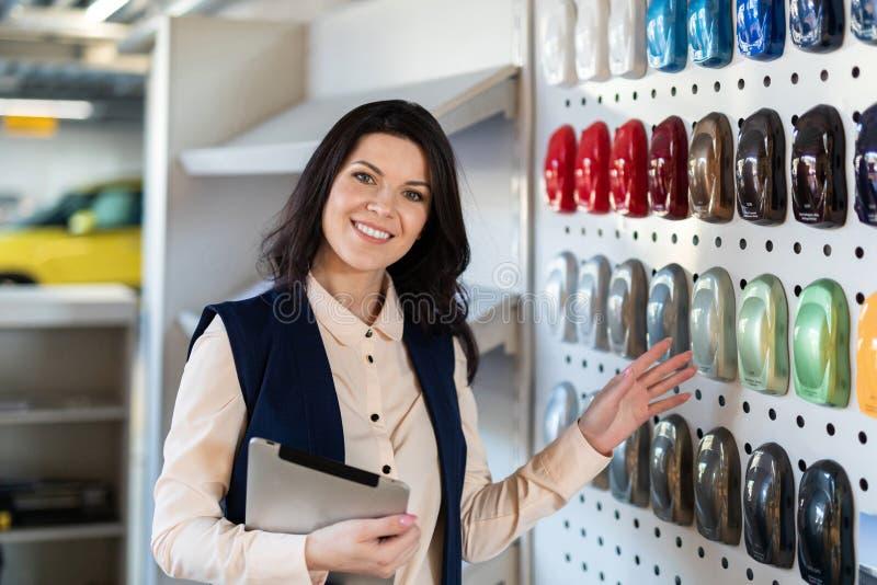 专业推销员帮助对选择了一辆汽车的颜色在经销权中心 免版税库存图片