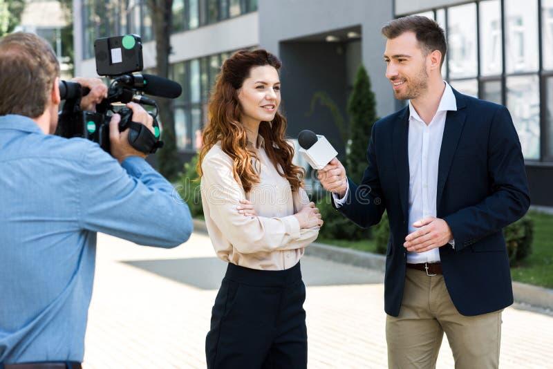 专业摄影师和男性新闻记者采访的微笑的女实业家 库存图片