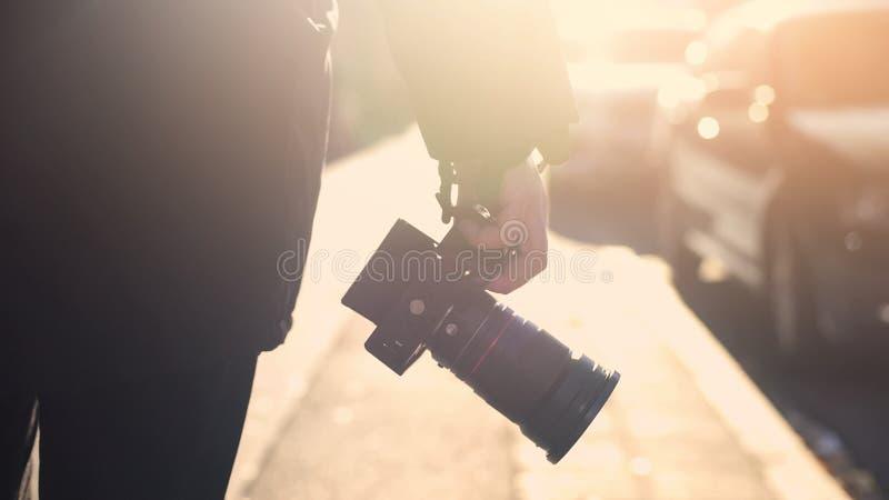 专业摄影记者藏品照相机,走在街道上,无固定职业的摄影师暗中侦察 库存照片