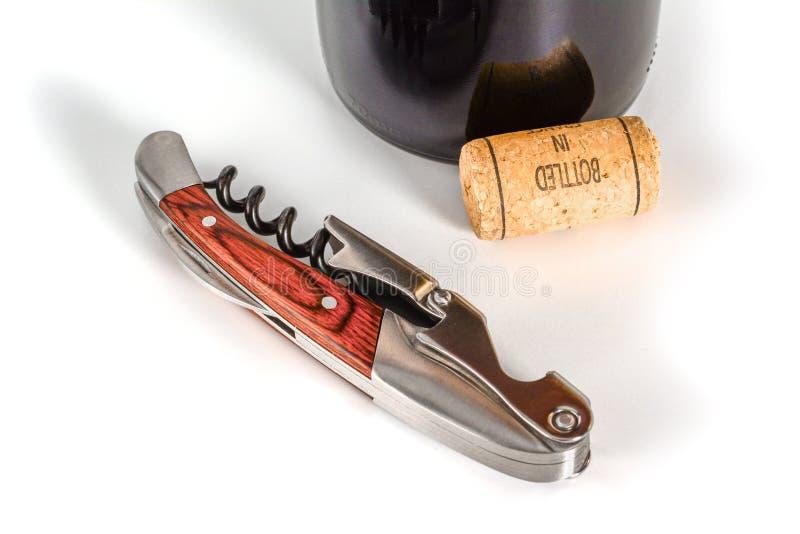 专业斟酒服务员或侍者刀子、拔塞螺旋和瓶盖启子关闭宏指令 关闭,与瓶和黄柏 免版税库存照片