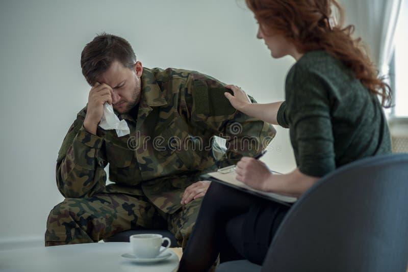 专业有战争综合症状的精神病医生支持的哭泣的战士在办公室 免版税库存照片