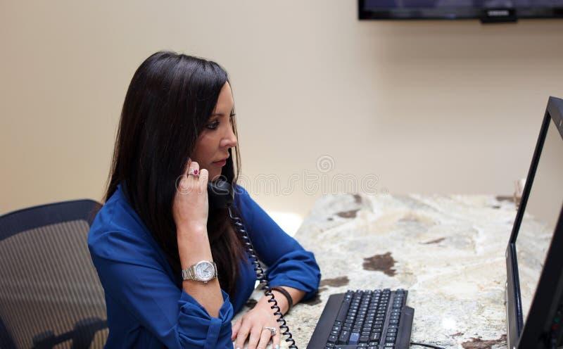 专业有计算机和回答的电话心理学家女性医生黑发谈话与客户 免版税库存照片