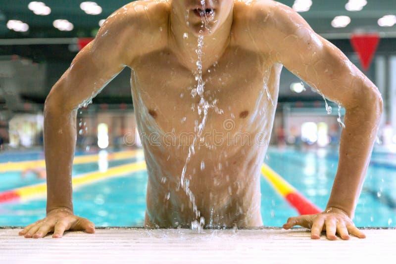 专业游泳者从水池涌现 图库摄影