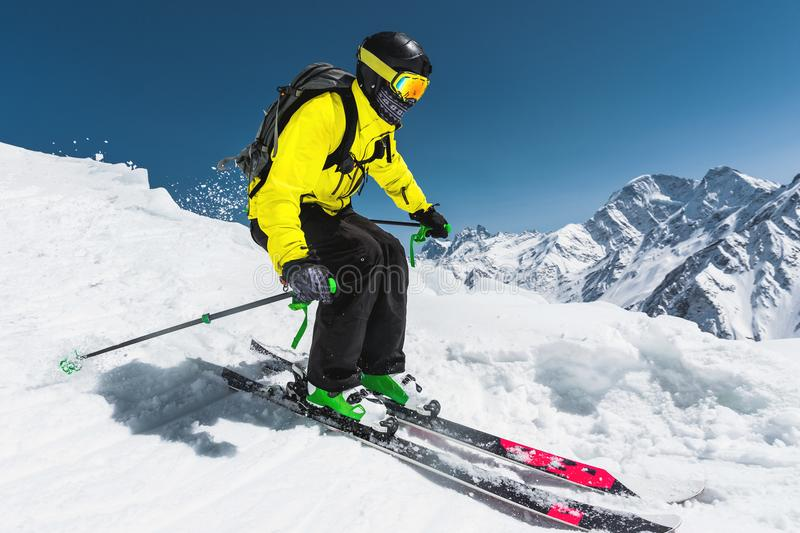 专业滑雪者以在跳跃的速度从冰川前在冬天反对蓝天和山 库存照片