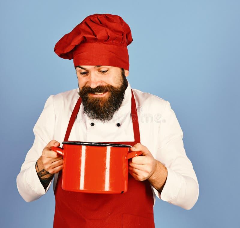 专业烹调法概念 有红色砂锅或平底深锅的厨师 免版税库存照片
