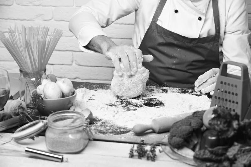 专业烹调法概念 男性手工用在白色砖背景的被揉的面团 免版税库存图片