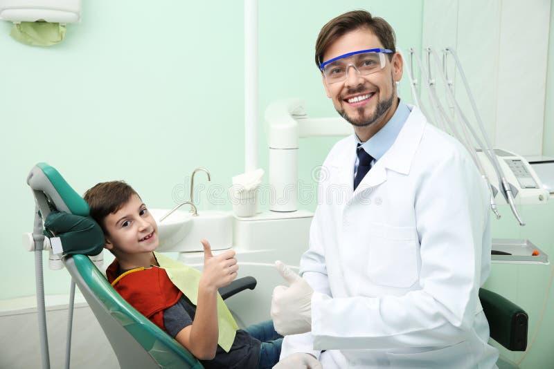 专业牙医和愉快的矮小的患者诊所的 库存图片