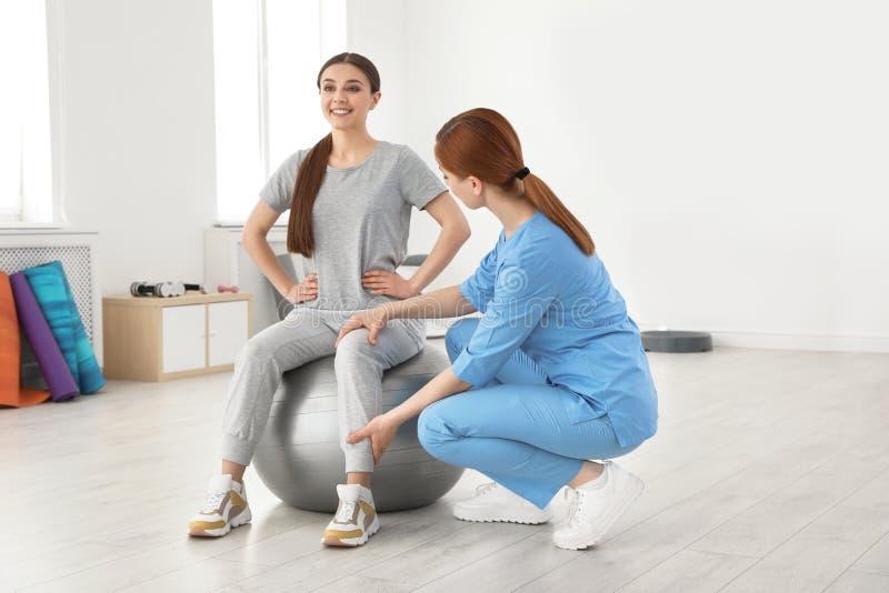 专业生理治疗师与女性患者一起使用 图库摄影