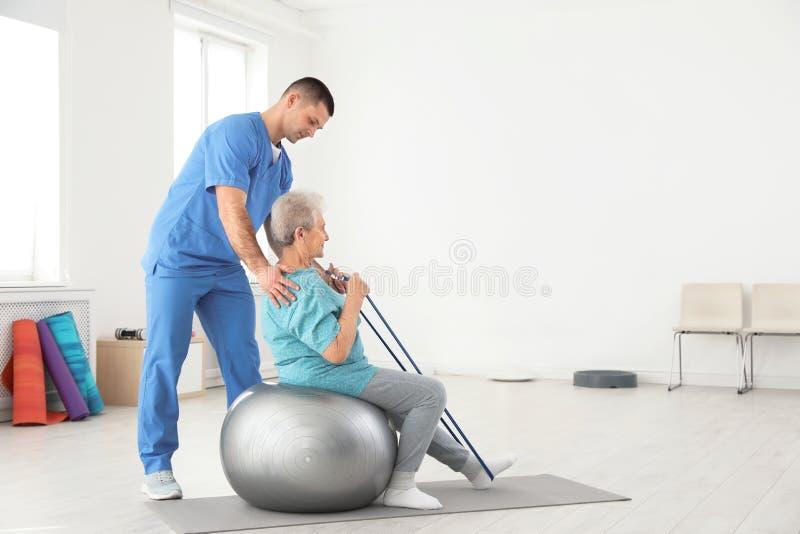 专业生理治疗师与年长患者一起使用在康复中心 库存照片
