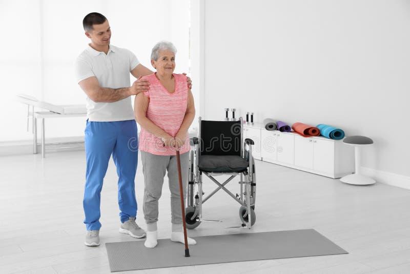 专业生理治疗师与年长患者一起使用在康复中心 免版税库存照片