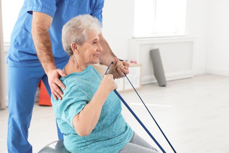 专业生理治疗师与年长患者一起使用在康复中心 免版税库存图片