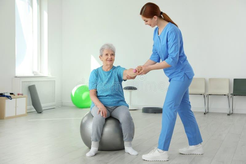 专业生理治疗师与年长患者一起使用 免版税库存照片