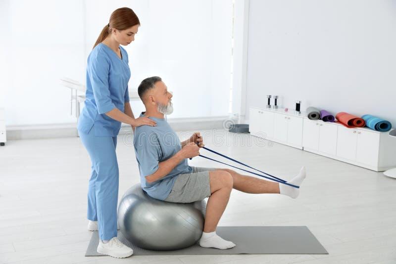 专业生理治疗师与资深患者一起使用 库存图片