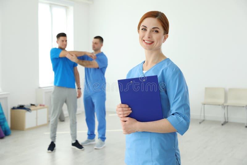 专业生理治疗师画象有剪贴板的在康复中心 免版税库存图片
