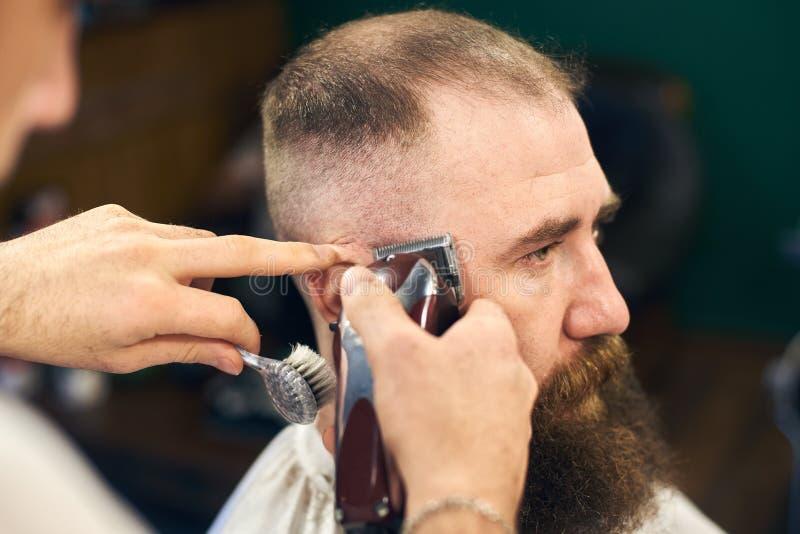 专业男性短haircutting有胡子的客户的在理发店 年轻理发师与电剃刀一起使用 ?? 免版税库存图片