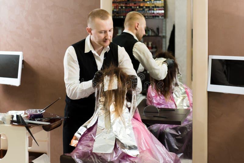 专业男性美发师与女孩的头发一起使用 免版税库存图片