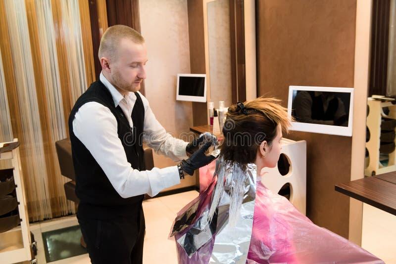 专业男性美发师选择染发剂颜色在现代沙龙,女性顾客变动发色 免版税库存图片