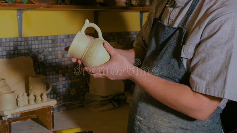 专业男性陶瓷工审查的水罐在车间 图库摄影